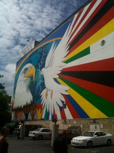 Mural of eagle and multi-colored rays on the side of a building