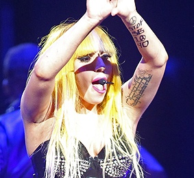 Lady Gaga performing with her hands raised, and the words 'STOP SB70' written on her left arm