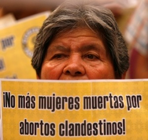 "Women holding sign ""No mas mujeres muertas por abortion  clandestinos!"""