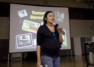 Gaby Rodriguez, a high school senior, standing with a microphone in front of a slideshow presentation