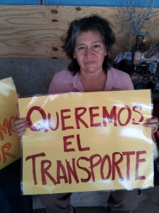 "Activist holding up a sign that says ""We want transportation"""