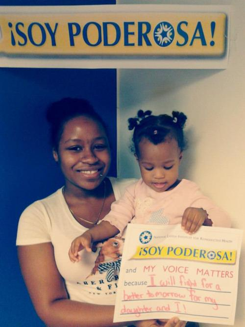 "Young woman holding her child, who is holding a sign that says ""Soy Poderosa and my voice matters because I will fight for a better tomorrow for my daughter and I"""